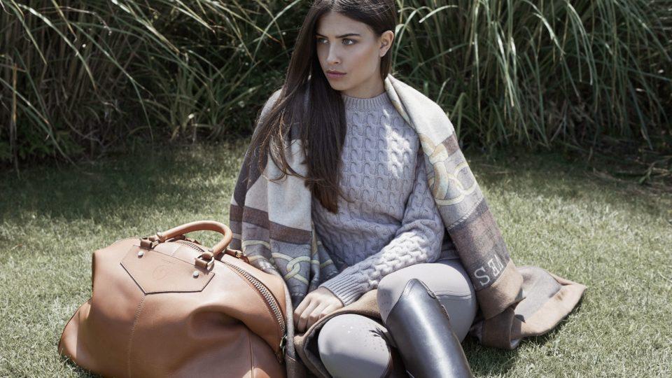 bild på tjej med stickad tröja och filt från Vestrum, matchat med en snygg handväska från vestrum